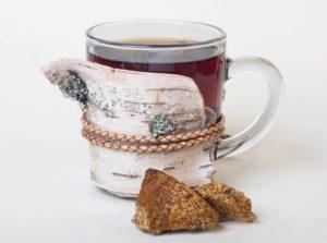 Chaga Pilz Tee im Glas vor weissem Hintergrund